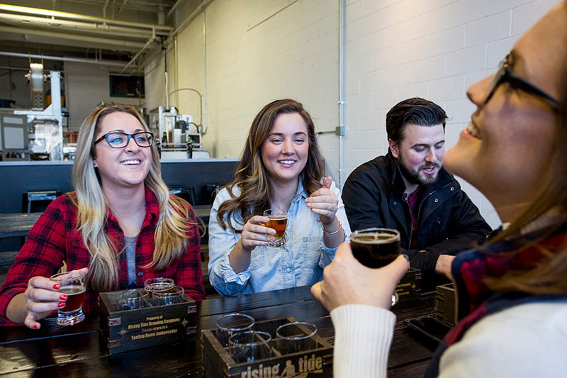 From left, Aimee Burbos, 24, and Samantha Schulte, 25, both of Portland, share a laugh with friend Kristen Hamilton, 24, of Boston, as they drink beers at Rising Tide's tasting room.