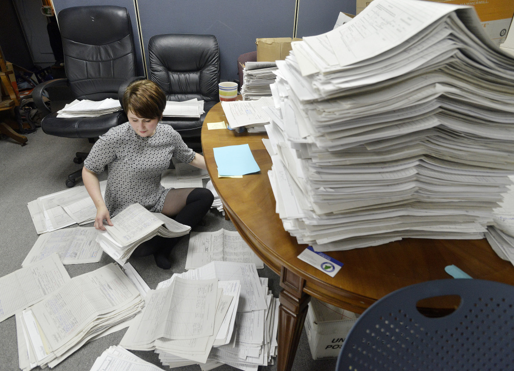 Allison Cormier, a volunteer for the marijuana legalization campaign, sorts petitions at the office in Falmouth.  John Ewing/Staff Photographer