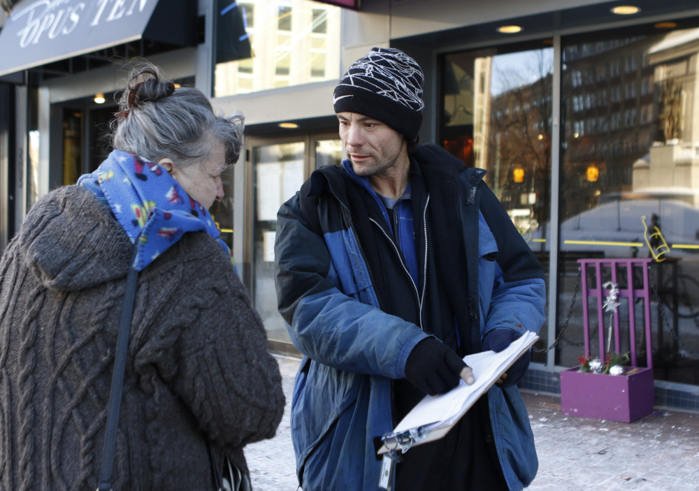 Brandon Scott speaks with Joyce Lorraine on Jan. 21 as he works to collect signatures in Monument Square in Portland on a petition for a casino referendum.