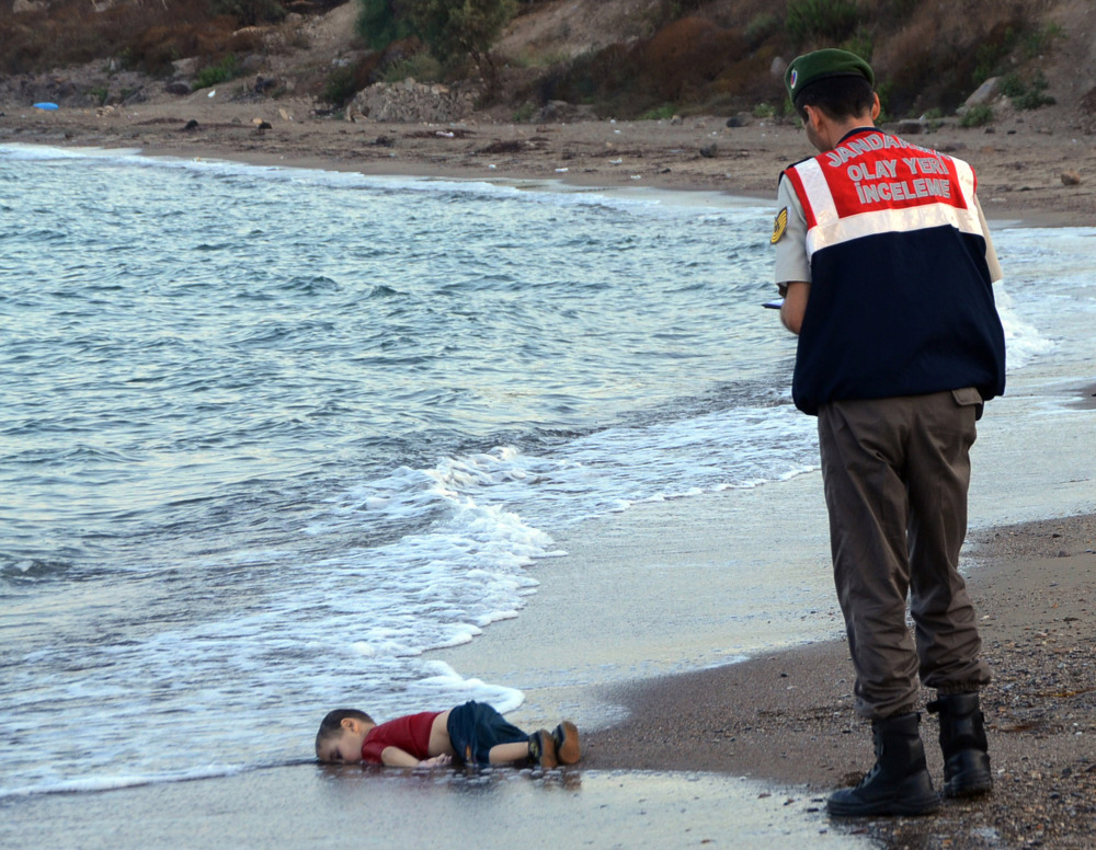 Sept. 2, 2015: A paramilitary police officer investigates the scene before carrying the body of 3-year-old Aylan Kurdi from the sea, near the beach resort of Bodrum, Turkey.