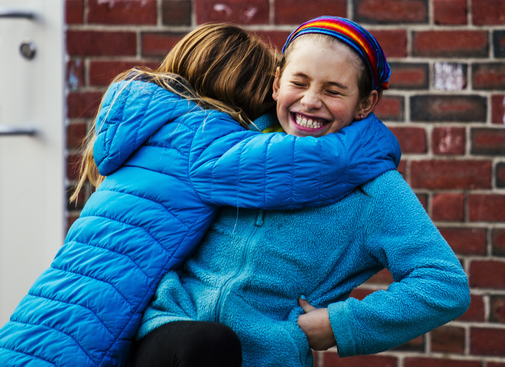 "Lucy Tidd, right, is embraced by a classmate after playing a round of four square during recess at Lyseth Elementary School in Portland on Jan. 27. Fellow students have been ""very accepting,"" Principal Lenore Williams said."