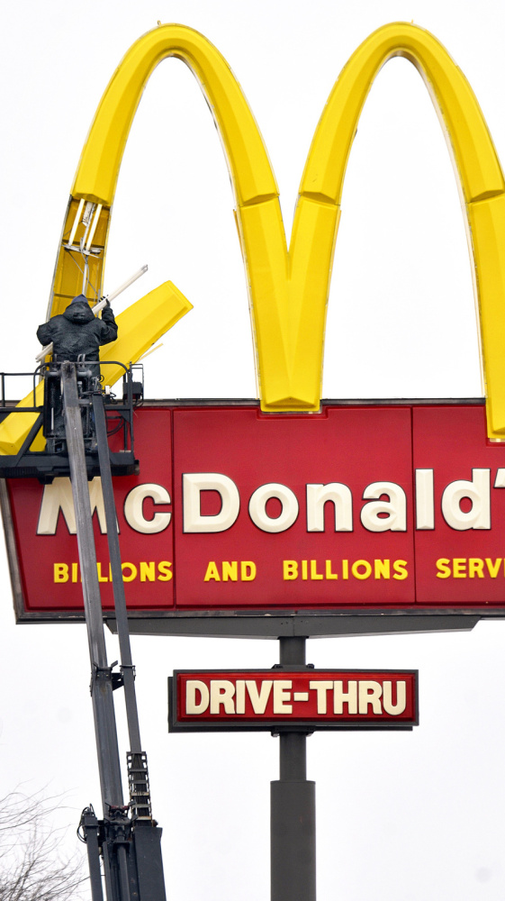 An installer changes bulbs in a McDonald's restaurant sign in Marion, Ind., on Monday.