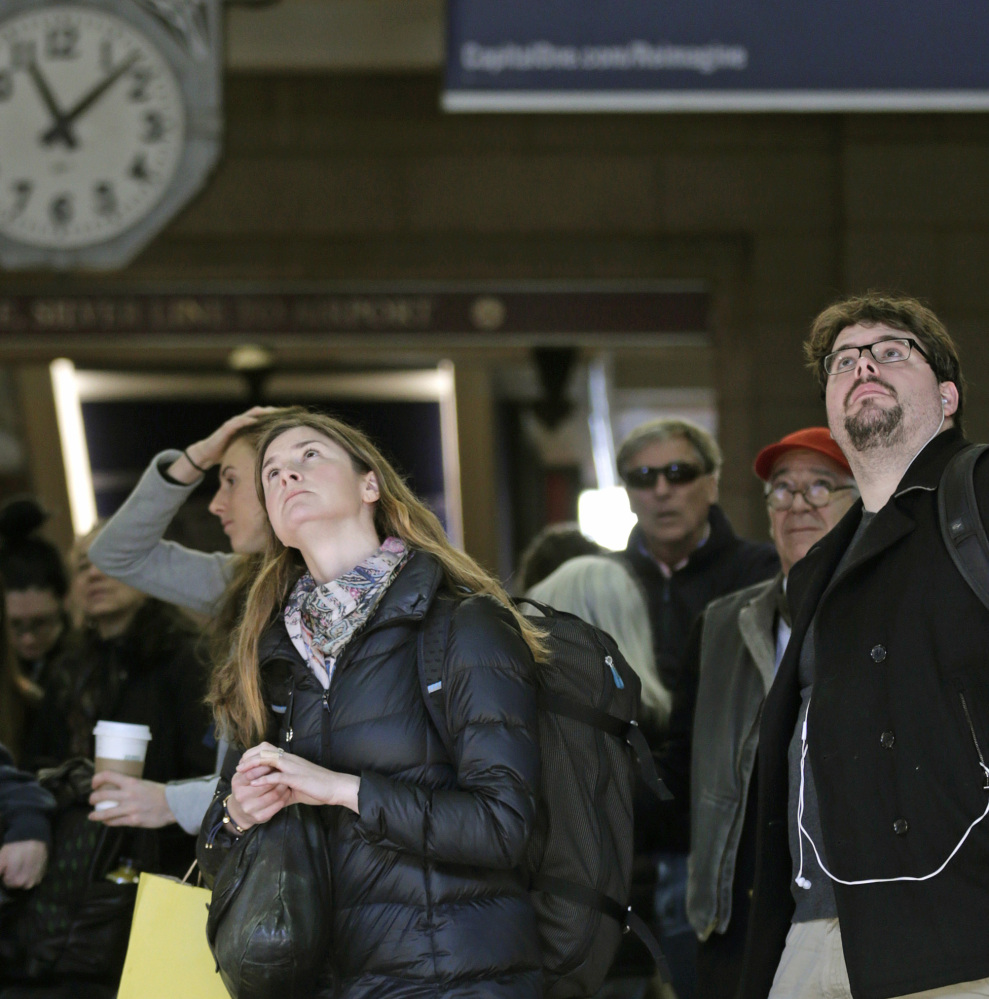 Travelers watch the train departure board at Boston's South Station Thursday for delays and cancellations.