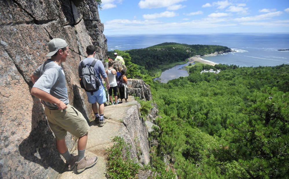 Hikers file up the Beehive Trail at Acadia National Park. All too often, pollution not only clouds the air at the park but also makes it hard for Acadia visitors to breathe.