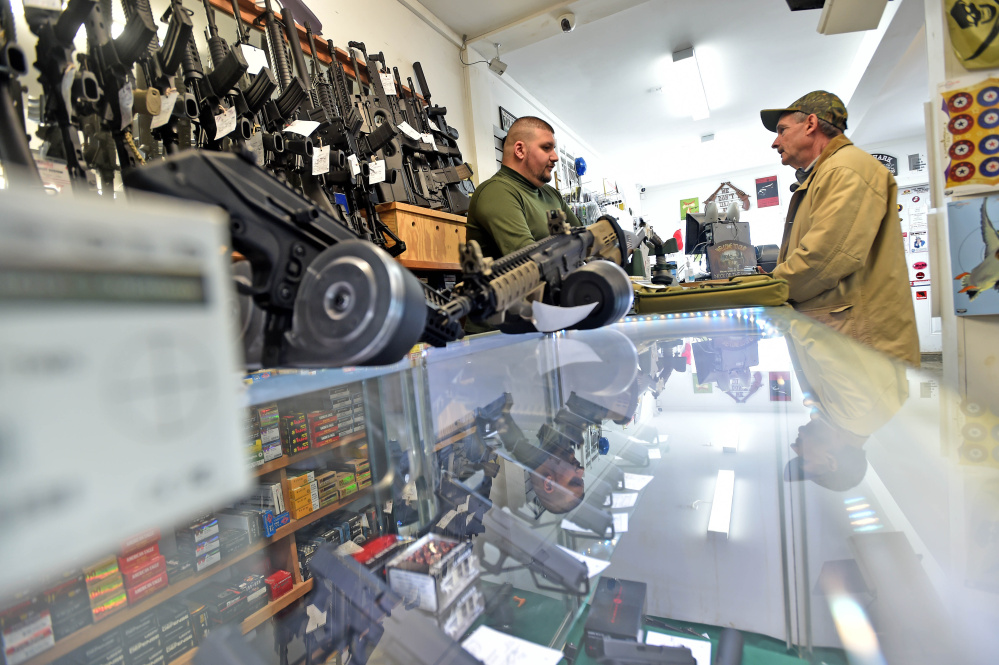 Amos Herrera, left, helps Neil Wooley of Vassalboro buy a handgun Friday at Fox Firearms Sales & Training Service in Vassalboro.