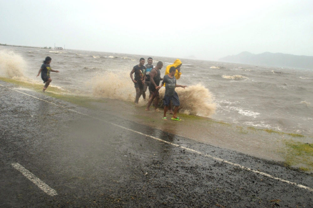 People are splashed by a wave whipped up by the approaching Cyclone Winston in Labasa, Fiji, on Saturday.