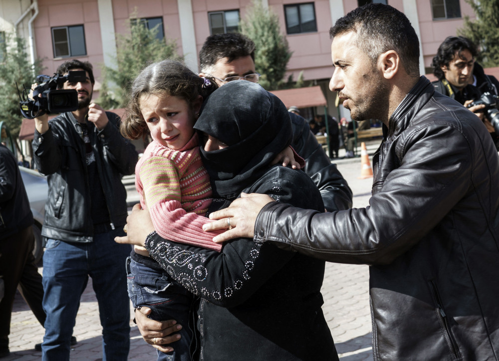 "A Syrian woman carries a wounded child Feb. 16. The main Syrian rebel group said Saturday it is ready ""in principle"" to implement a provisional truce in the 5-year civil war."
