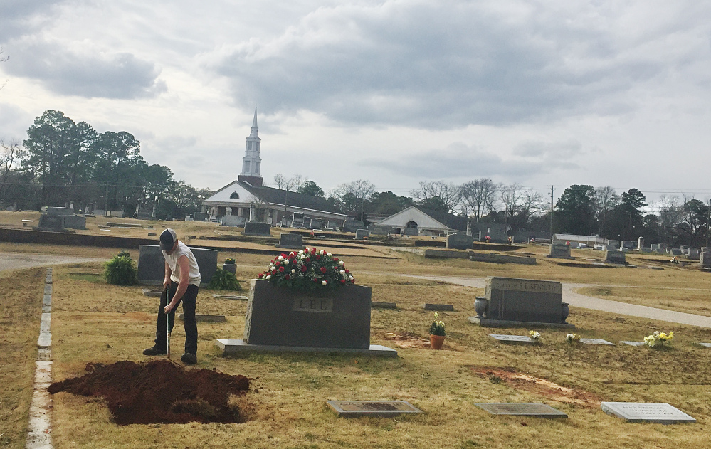 A man rakes dirt over a grave in the Lee family cemetery plot, Saturday in Monroeville, Ala.