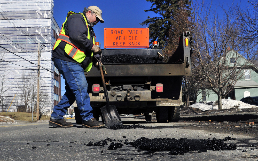 Augusta city employee Bill Jackman fills a pothole on Sewall Street in Augusta on Friday.
