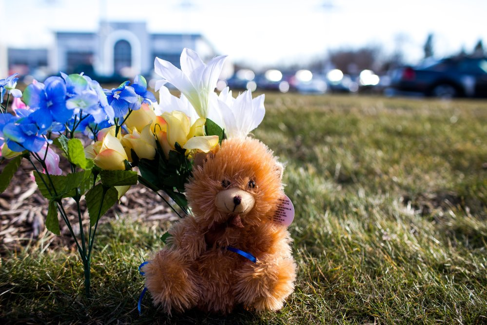 A makeshift memorial is seen near where people were shot near car dealership Sunday in Kalamazoo, Mich.