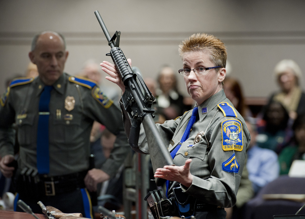 In this Jan. 28, 2013, file photo, firearms training unit Detective Barbara J. Mattson, of the Connecticut State Police, holds up a Bushmaster AR-15 rifle, the same make and model of gun used by Adam Lanza in the Sandy Hook School shooting, during a hearing of a legislative subcommittee, at the Legislative Office Building in Hartford, Conn.
