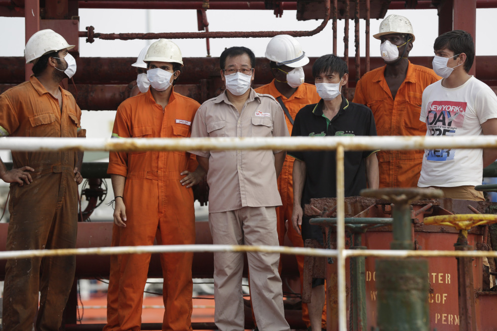 Rescued crew of the hijacked Maximus vessel stand for the media in Lagos, Nigeria, on Monday. The ship has been hijacked three times in five years in the Gulf of Guinea. The Nigerian navy stormed the ship, which bandits wanted for its diesel fuel.