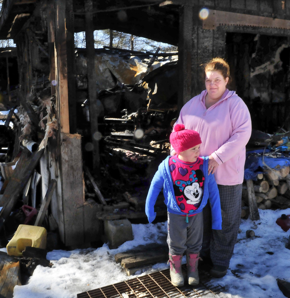 """Tornia Bowring and her granddaughter, Serenity, stand outside Monday at the Norridgewock home they lived in when it was destroyed by fire last month. Tornia, and her children and husband, were subjected to a vicious social media campaign after the fire, and are now living in a camper. """"I'm still grateful for all the support that people have shown ...,"""" she says."""