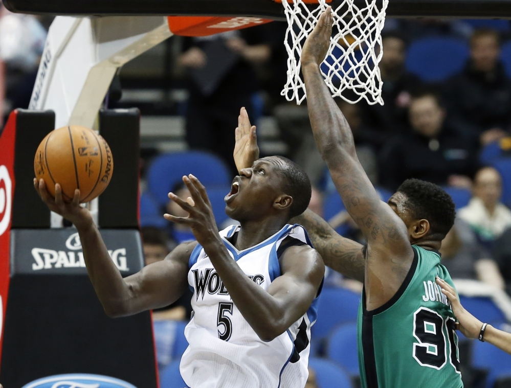 The Timberwolves' Gorgui Dieng eyes the basket as Boston's Amir Johnson defends in the first quarter.