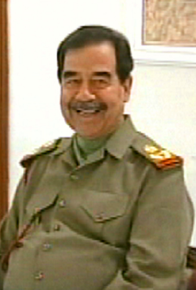 Iraqi President Saddam Hussein smiles as he talks with his son Qusai in this image broadcast on Iraqi television on Sunday, March 23, 2003. The exact date and location of the video are unknown. (AP Photo/Iraqi TV via APTN)