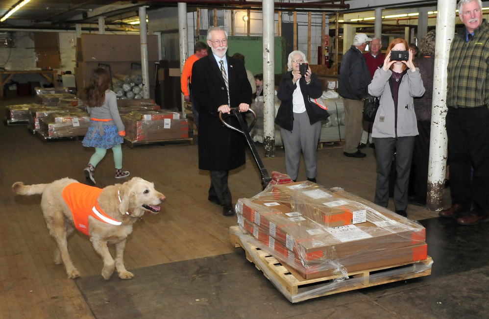 The Swains' dog, Max smartly models a vest Wednesday while state Sen. Rod Whittemore helps load pallets of Dog Not Gone Visibility Products on an Arkansas-bound truck.
