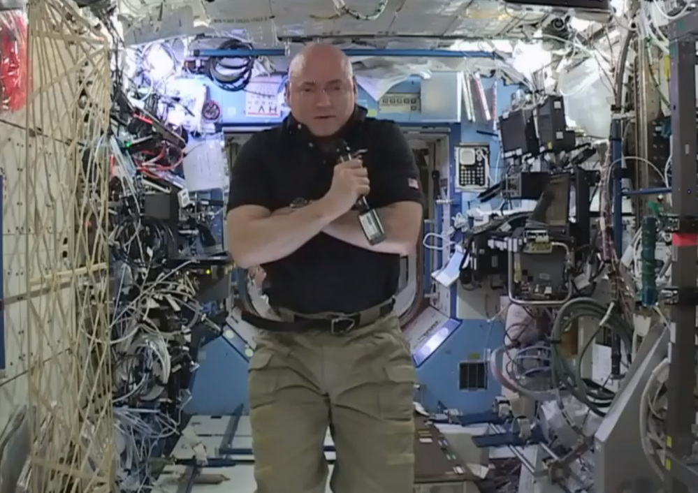 Astronaut Scott Kelly speaks to reporters during a news conference held from the International Space Station on Thursday. After nearly a year in space, Kelly is just a few days away from returning to Earth. At left, in image from video made available by NASA on Tuesday, Kelly wears a gorilla costume, a gift from his identical twin brother, former astronaut Mark Kelly.