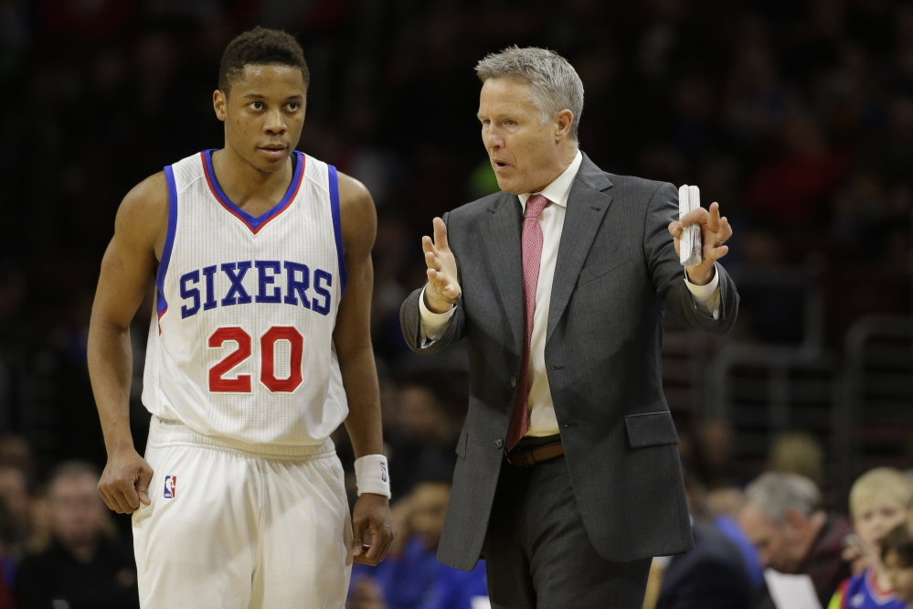 Philadelphia 76ers' Brett Brown, right, talks with Tim Frazier during an NBA basketball game against the Indiana Pacers last February. The Associated Press