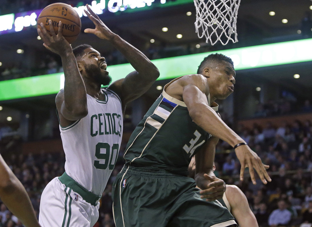 Celtics forward Amir Johnson scores against Milwaukee forward Giannis Antetokounmpo in the first quarter Thursday night in Boston.