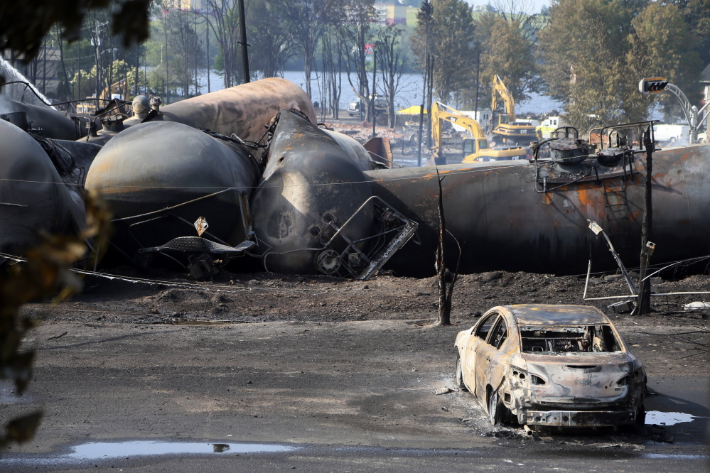 A burnt-out vehicle sits near a train derailment in Lac-Megantic, Quebec, in 2013. A report by the U.S. Department of Transportation's inspector general is calling for greater accountability by federal regulators to prosecute rail safety violations.