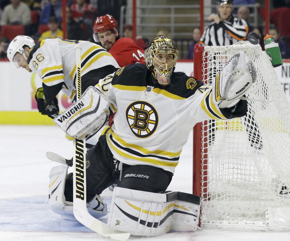 Bruins goalie Tuukka Rask deflects a shot in the second period of Friday night's game at Raleigh, North Carolina.