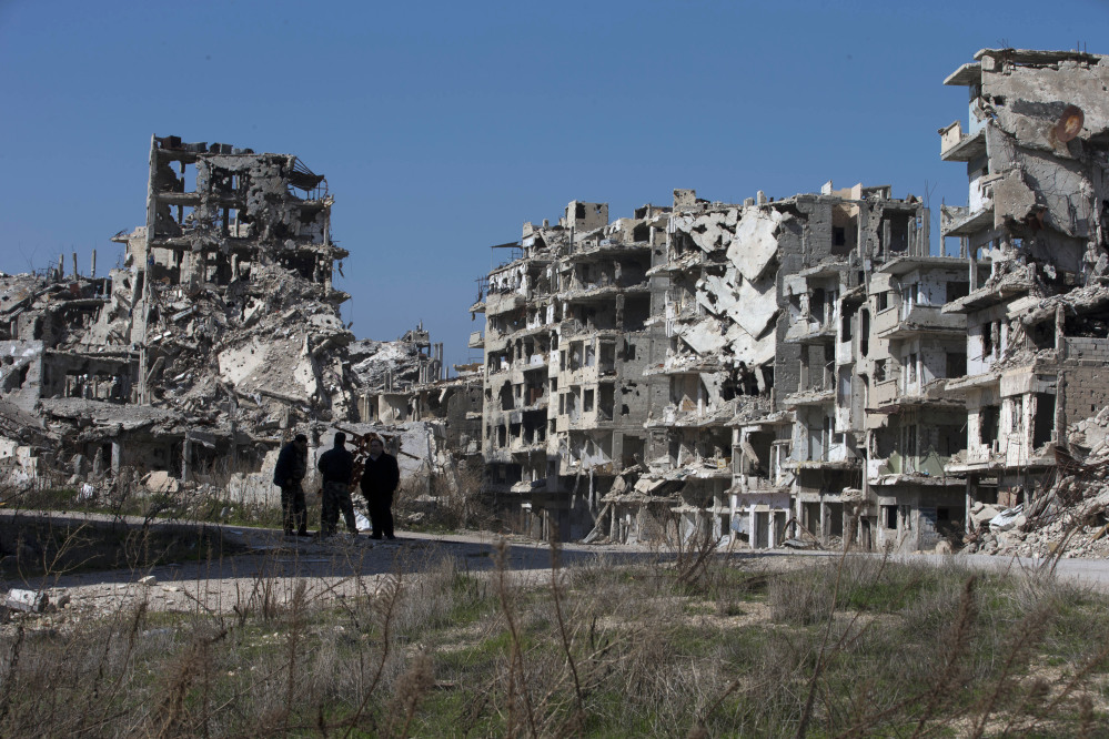 Syrian men walk through a devastated part of the old city of Homs, Syria.