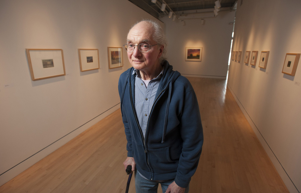 UMaine art instructor Michael Lewis poses for a portrait at Lord Hall Gallery, where 52 pieces of his art hang.  Kevin Bennett/Staff Photographer