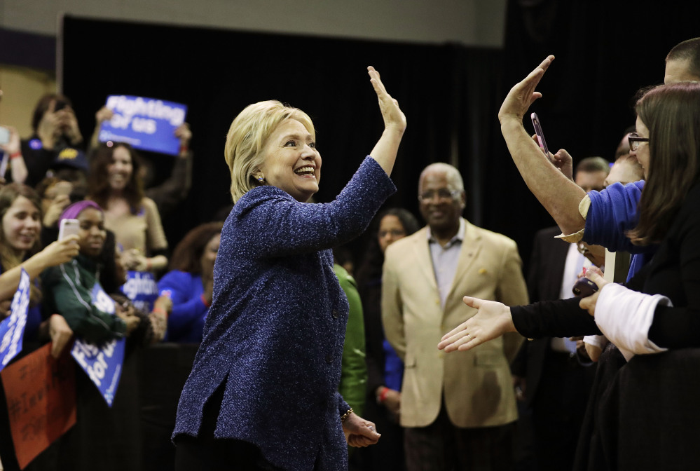Democratic presidential candidate, Hillary Clinton high-fives an audience member as she arrives for a campaign event at Miles College Saturday, Feb. 27, 2016, in Fairfield, Ala. (AP Photo/David Goldman)