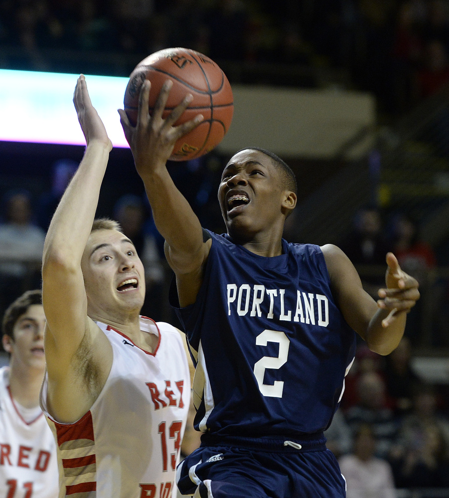 Portland's Terion Moss drives to the basket against South Portland's Jack Fiorini in the Class AA boys' basketball state championship game Saturday at Cross Insurance Arena.