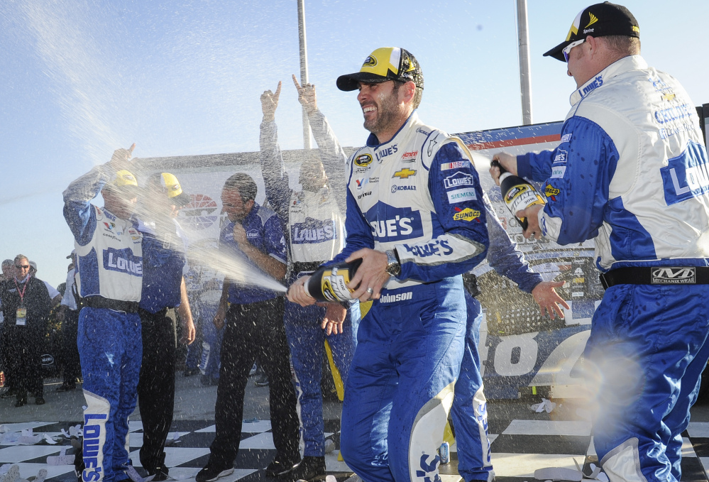 Jimmie Johnson, second from right, celebrates with team members after winning the Sprint Cup Series race Sunday at Atlanta Motor Speedway in Hampton, Georgia. The victory was the 76th of Johnson's career.