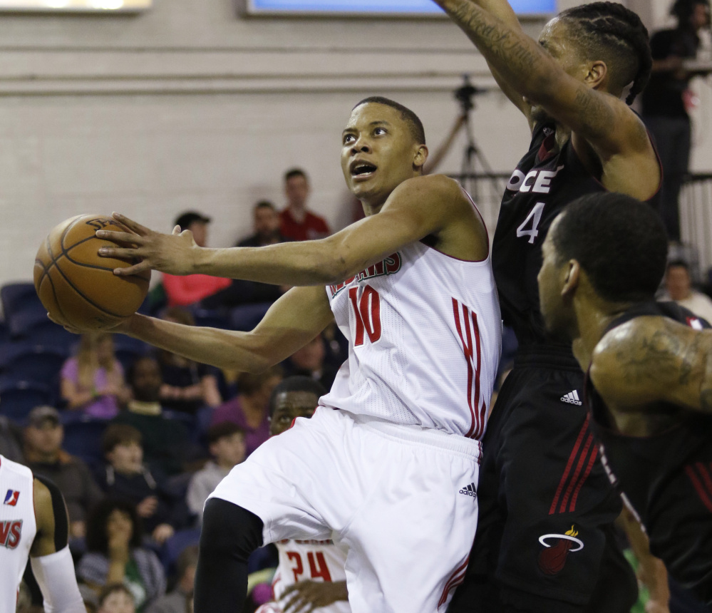 Tim Frazier goes up for a shot Sunday against Rodney McGruder of the Sioux Falls Skyforce during the Maine Red Claws' 132-111 win at the Portland Expo. Frazier recorded a triple-double with 24 points, 12 rebounds and 12 assists.