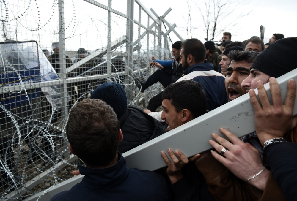 Refugees and migrants try to break an iron fence from the Greek side of the border as Macedonian police stand guard, near the northern Greek village of Idomeni on Monday. Macedonian police fired tear gas and stun guns as several hundred Iraqi and Syrian refugees, frustrated at days of delays in crossing the Greek-Macedonian border, broke down a gate on a nearby rail crossing.