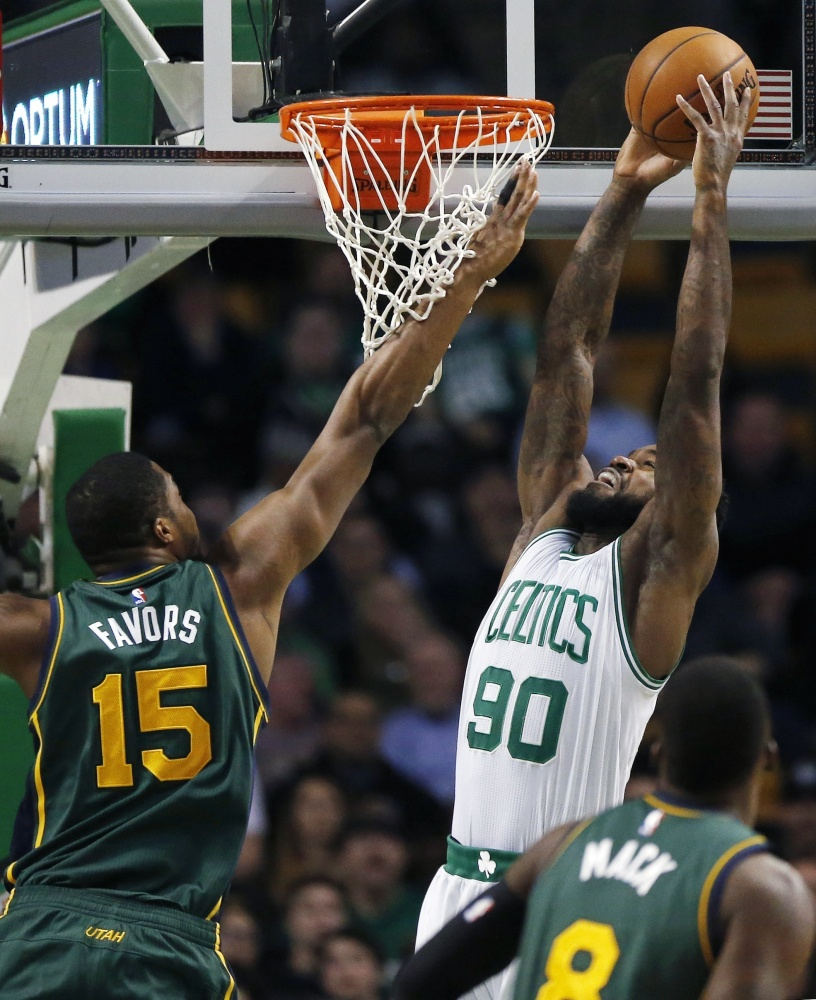 Boston's Amir Johnson goes for a shot against Utah's Derrick Favors in the first quarter.