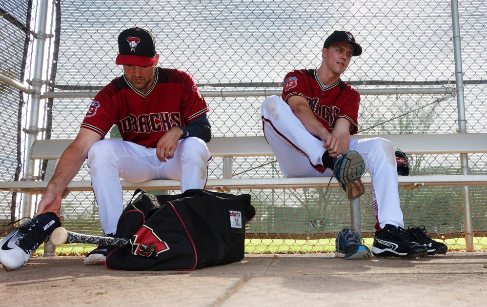 Arizona pitchers Zack Greinke, right, and Robbie Ray change out of their spikes after a workout during a spring training session Monday at Scottsdale, Arizona.