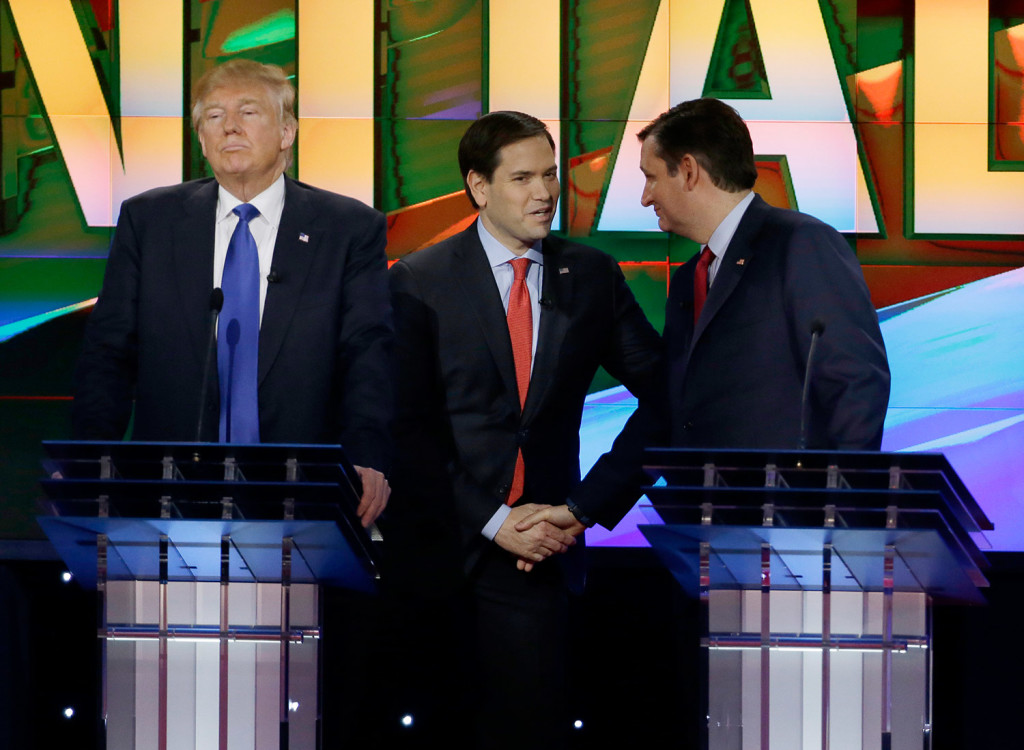 Donald Trump pauses as Marco Rubio and Ted Cruz greet each other during a break in the Republican presidential debate Thursday night at the University of Houston. The Associated Press