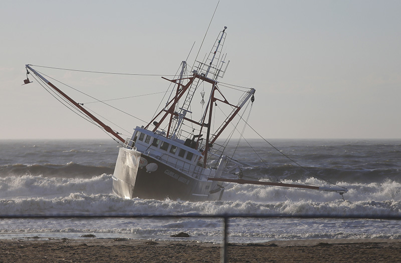 Fishing boat, the Carolina Queen III, rests in shallow water just off Rockaway Beach.