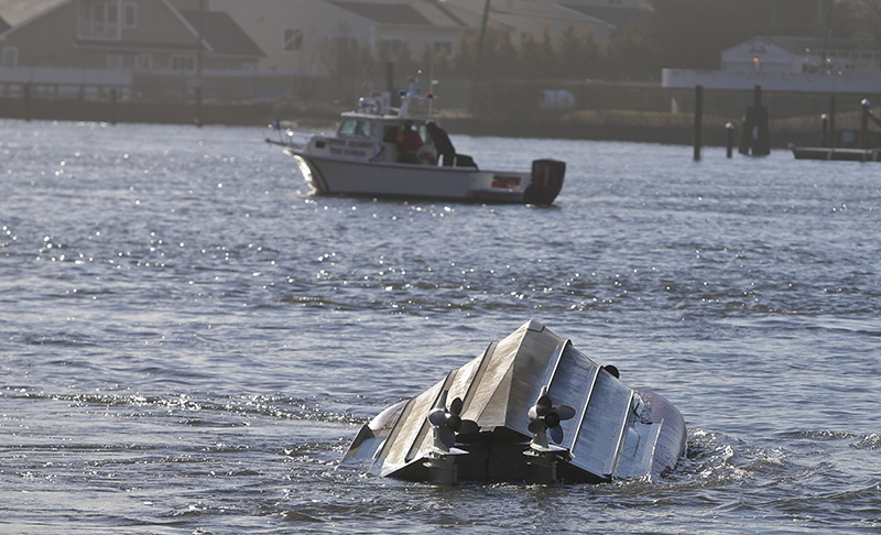 A Fire Rescue vessel passes a Coast Guard vessel that has overturned on Thursday off of Queens.
