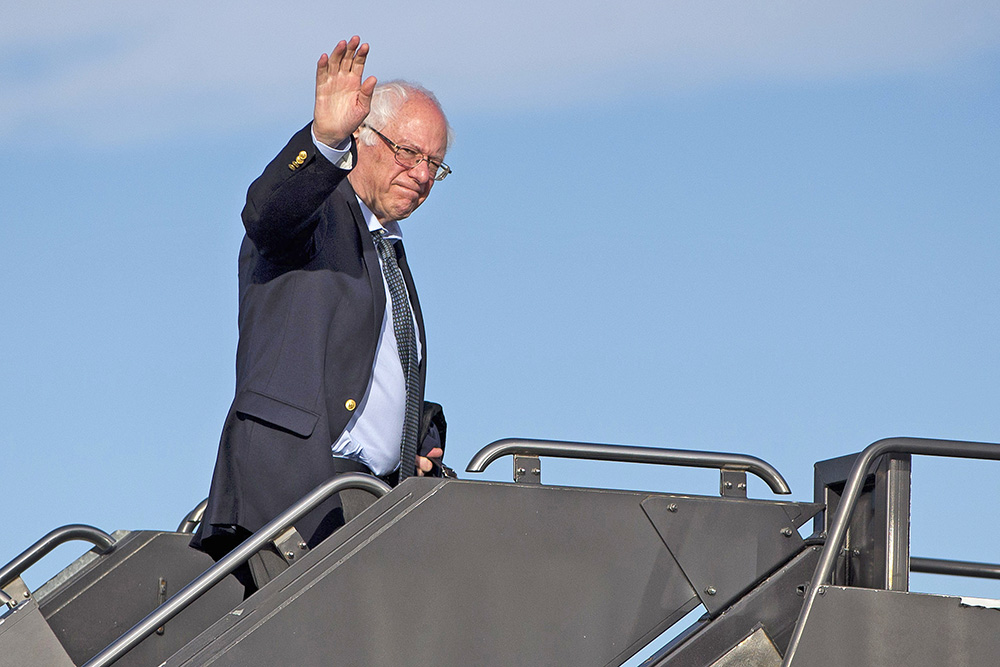 Democratic presidential candidate Sen. Bernie Sanders, I-Vt. waves as he boards his plane in Denver Monday,en route to Minnesota. The Associated Press