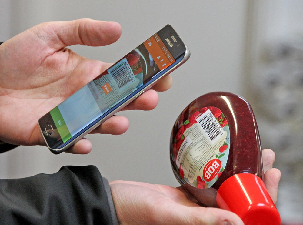 Swedish entrepreneur Robert Ilijason shows how to use a cellphone to scan a purchase at the no-staff shop in the southern Sweden village of Viken. The Associated Press