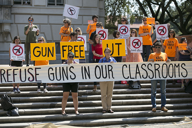 In this October, 2015 photo, protesters gather on the West Mall of the University of Texas campus to oppose a new state law that expands the rights of concealed handgun license holders to carry their weapons on public college campuses.