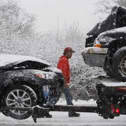 Greg Fulda of Pleasant Hill Auto Sales checks a couple of cars before towing them from the scene of an accident at the corner of Payne and Milliken roads in Scarborough. According to Fulda, six vehicles were involved in the crash.