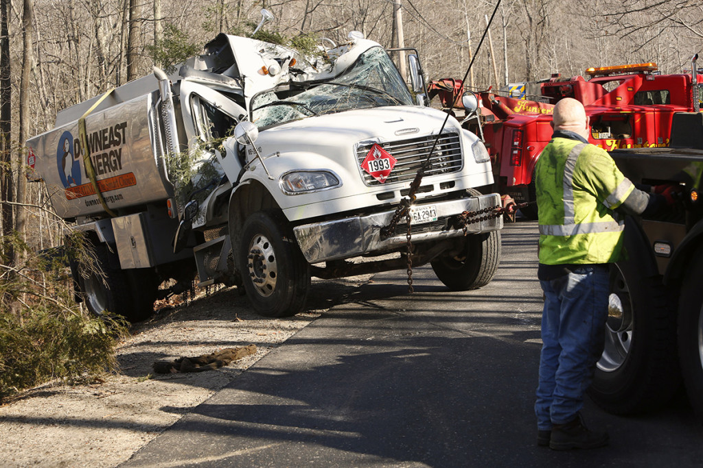 An oil truck that tipped off the edge of Hunter Road in Freeport is pulled back onto the road by a wrecker crew Monday morning.