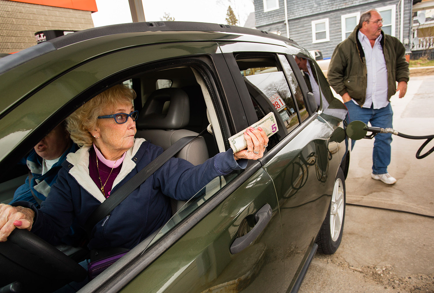 Deanna Mitchell of Westbrook holds her money out the window as Westbrook Auto Center owner Tom Allard puts gas in her tank.