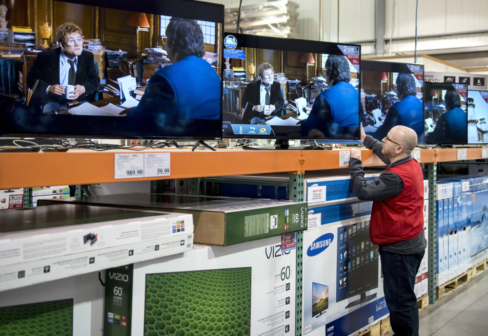 An employee adjusts a TV set at a store in Ottawa, Ontario, on Tuesday as Canada begins phasing in a choose-your-channels system. The change may answer the question of who will win and lose if every channel goes it alone.
