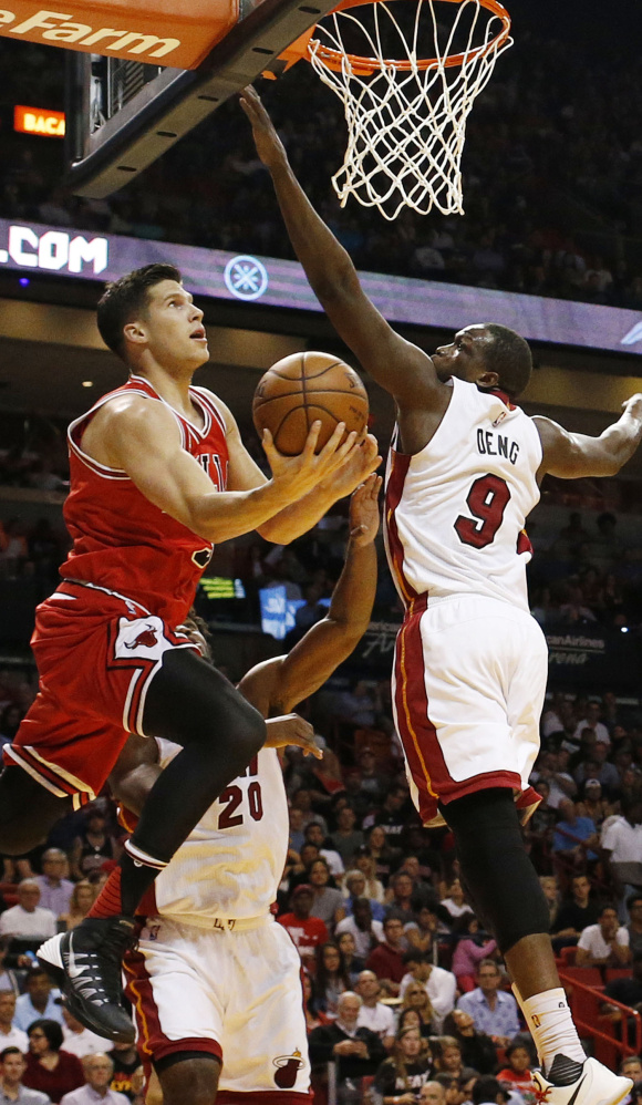 Doug McDermott of the Chicago Bulls attempts to lay the ball up over Luol Deng of the Miami Heat during the first half of Miami's 129-111 win Tuesday.