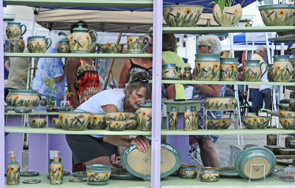 Sue Firlotte of North Monmouth checks out a platter in The Potter's House booth during the Winthrop Summer Festival last August, when Maine was in the midst of strong third-quarter growth that ranked 16th in the nation.