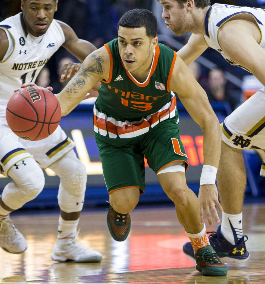 Miami's Angel Rodriguez drives between Notre Dame's Demetrius Jackson, left, and A.J. Burgett  during the first half Wednesday night. Rodriguez had 19 points in Miami's 68-50 road win.