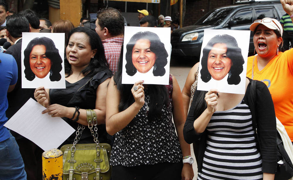 People hold photos of slain Honduran environmentalist and indigenous leader Berta Caceres at the coroner's office in Tegucigalpa on Thursday. The mother of four was 40.