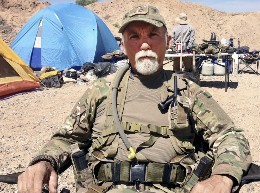 "Gerald ""Jerry"" DeLemus of Rochester, N.H., sits among a group of militia members camping on Cliven Bundy's ranch near Bunkerville, Nev., in 2014."