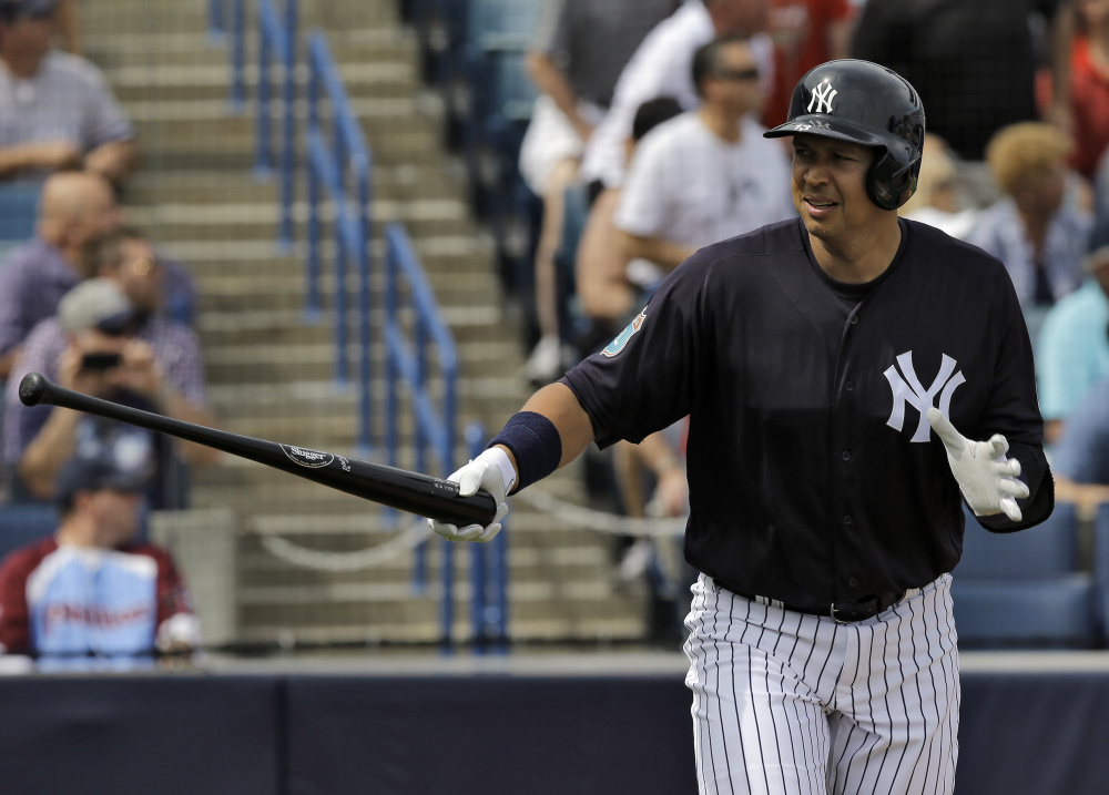 Alex Rodriguez of the Yankees hands his bat to a batboy Thursday after hitting a two-run home run off Philadelphia pitcher Adam Morgan in the first inning of a 13-4 spring training win for New York at Tampa, Florida. The homer came in Rodriguez's first at-bat of the spring.